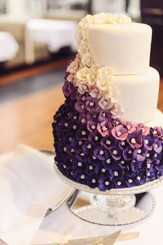A three-tiered cake with an ombré cascade of tiny flowers #purple #cake #wedding