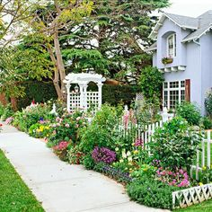 Front Yard Sidewalk-Garden Ideas: Grow a Cutting Garden.   Even though they take up little real estate, small-space sidewalk gardens can be great for growing your own cut flowers. Here, foxgloves, roses, and a host of other flowers are perfect for dressing up the front of the house and dropping in a vase for a great hostess gift or table decoration.