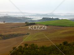 Plowed Tuscan Fields - Morning shot of plowerd fields over the Tuscan hills with fog banks in the distance.