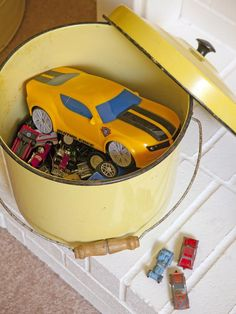 old enamel pot from a junk store turned into CUTE KiDs toy storage on the fireplace hearth . . cute, cheap, easy way to hide all those HoT WHeels! from our BIG HAPPY FAMILY episode on HGTV {junk gypsy co. - http://gypsyville.com/ }