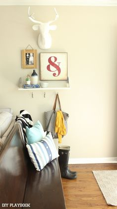 This entryway is all ready for the colder months ahead. Add hooks for jackets and a spot for snowy boots by your front door. #HappyByDesign #sponsored