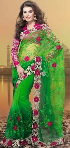 Exquisite combination of color, fabric can be seen here.   This green net saree is nicely designed with embroidered patch work is done with resham, zari, sequins and stone work.   Beautiful embroidery work on saree make attractive to impress all.   This saree gives you a modern and different look in fabulous style.   Contrasting dark pink blouse is available.   Slight color variations are possible due to differing screen and photograph resolution.