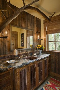 A tree branch in this rustic bathroom gives an unexpected touch.