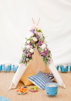 """A photo by Janis Nicolay from our """"Poppytalk for Target"""" launch event (picnic basket and blankets)! Launches on June 22. A Moozle plain reg or MIDI teepee would give the same effect as the tent here - just add flowers! :0) mmozlehome.com"""