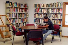 patron reading at table in Lower Brule Community College Library #SDSLCornerstone