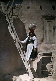 New Mexico - Water carrier stands on ladder in New Mexico Acoma Pueblo. Three reservations make up Acoma Pueblo: Sky City (Old Acoma), Acomita, and McCartys. The Acoma Pueblo tribe is a federally recognized tribal entity. The Acoma have continuously occupied the area for over 800 years. Today, about 300 two and three-story adobe buildings reside on the mesa, with exterior ladders used to access the upper levels where about 30 residents live without electricity or running water.
