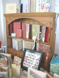 The bookshelf makes it feel like home! Cool sign too. Craft show booth for handmade books