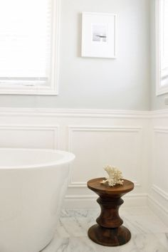 Beautiful light grey bathroom with white millwork/panelling.