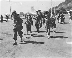 Italian children helping American soldiers with their equipment
