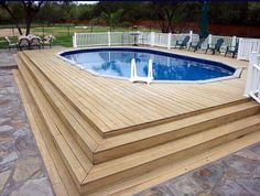 Oval in-ground swimming pool designs with wooden decks and flagstone