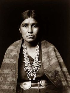 You are looking at an intriguing picture of a Navajo Woman. It was taken in 1904 by Edward S. Curtis.    The picture presents a Navajo woman wearing silver squash blossom necklace, concho belt, blanket draped over shoulders.    We have created this collection of pictures primarily to serve as an easy to access educational tool. Contact curator@old-picture.com.    Image ID# 6C989895