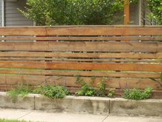 Horizontal wood slat fence with concrete base: totally different feel than the traditional picket fence. And it uses a bit less wood.