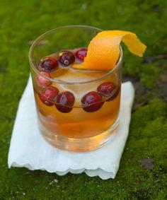 Old Fashioned Cocktail: 1 teaspoon sugar, Dash bitters, an orange twist or an orange slice, 2 ounces bourbon, a few ice cubes, fresh cranberries for garnish
