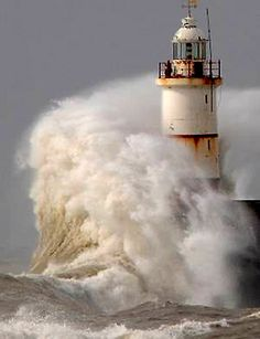 Light house taking a wave