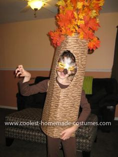 """Homemade Owl in a Tree Costume [Glued] fabric that looked like a tree trunk...to cardboard...cut holes for her head & arms...hot glued stems with leaves on...[used] iron on Velcro strips to close the back...so it would make easy access to put it on & take it off. The mask was ...an assorment of brown, tan, black and white feathers...glued...to a mask that was purchased at the craft store."""
