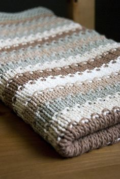 knit blanket. Knitted in stockinette stitch with seed stitch in between colors. Garter stitch border.