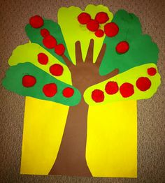 Apple tree- hand cut out for trunk, feet cut outs for tree leaves, red pom poms for apples