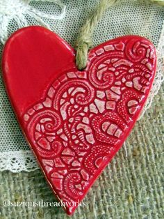 ceramic heart with a lacey design pressed into it.