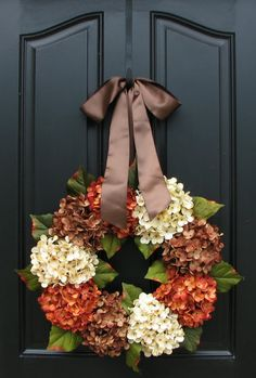 i'd just ditch the ribbon.  Half fall hydrangeas on a twig wreath with burlap.  Or sunflowers?