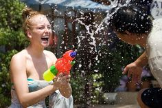 A foreign tourist shoots water at a man to celebrate the water festival which marks the country's new year in Vientiane, the capital of Laos, on April 13, 2012. The Laos new year, similar to Thailand's Songkran Festival which occurs at the hottest time of the year, is marked in a number of South and Southeast Asian nations and starts this year on April 13