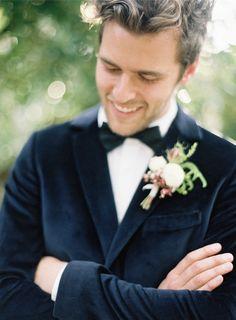 Handsome groom wearing a navy blue velvet tux.