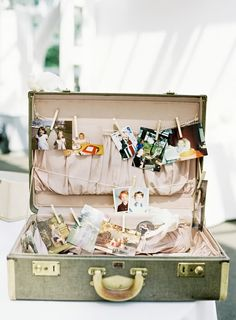 Vintage luggage used as photo display...Just finished this sort of thing using my Grandmothers suitcase today...above it hangs an old window frame with chicken wire and photos clothespinned to it...