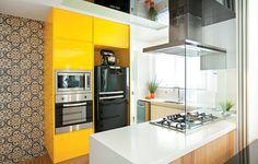 """O armário com laca brilhante amarelo gema deu o ar moderno à cozinha que é aberta para a sala. """"É uma cor divertida que faz uma contraposiçã..."""