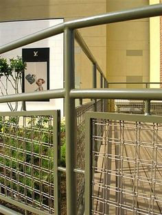 Banker Wire Mesh M22-27, a popular twin wire architectural mesh, often finds itself being used as railing infill panels, as it is here at an Austin, Texas shopping mall. The infill panels have a powder coated finish.
