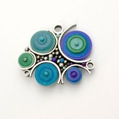 Something completely different from Liz Hall of Lizard's Jewelry. Fun Funky circle Brooch pin sterling silver with purple blue green quilling paper and polymer.