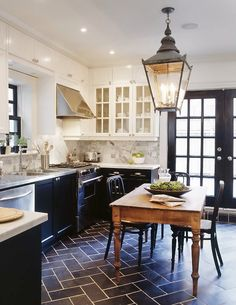 soft white uppers, black lower cabinets, dark gray on floor, unfinished wood table, exterior lantern light fixture- carriage house feel.