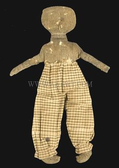 "Brown wool boy doll in woven wool pants with primitive embroidered features. Tag with doll reads: ""This doll belonged to Minnie Maynard, signed Ernest Cousin"". Dimensions: 15"" H."