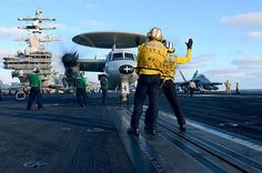 Aviation boatswain's mates direct an E-2C Hawkeye assigned to the Black Eagles of Carrier Airborne Early Warning Squadron (VAW) 113 to the catapult on the flight deck of the aircraft carrier USS Ronald Reagan (CVN 76). #USNavy #AircraftCarrier #ReaganCVN76