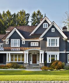 Love all the detail lines of this home's exterior; windows, stone porch, columns, metal roof, and color.