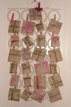 Advent gift calender made from an Ikea Komplement hanger, wooden pegs, brown envelopes and lots of tape...