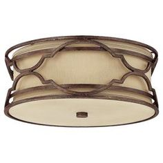 """Cast a warm glow over your den or entryway with this chic flush mount, featuring an openwork design around a fabric drum shade.     Product:  Flush mountConstruction Material: Metal and fabricColor: Bronze and gold dustFeatures:UL listed for damp locationsAccommodates: (3) 40 Watt medium base bulbs - not includedDimensions: 6.75"""" H x 16"""" Diameter"""