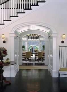 Archway Hall under Stairs toward Dining Room (Dutch Colonial in California by Tommy Chambers Interiors)-I like the dark wood stairs w/ light walls and white trim