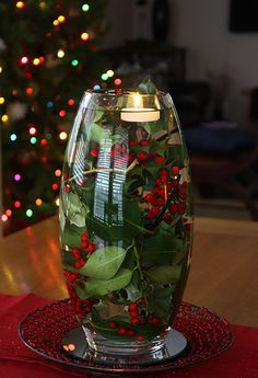 Christmas Decorating: holly leaves and berries in water-filled vase with floating tealight.  Gorgeous.