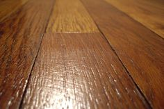 Regular weekly cleaning is key to a gleaming wood floor. Add a quarter of a cup of white vinegar to a gallon of warm water and use the mixture and a well rung-out mop to clean the floors, taking care not to over-wet the wood. It's actually better to use a vinegar mixture than oil soap or other detergent cleaners, because over time the soap will leave a build-up on your wood.