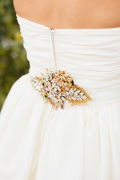Several vintage brooches put together to accessorize this wedding gown - Wedding On #SMP: http://www.StyleMePretty.com/2014/03/27/whimsical-woodland-garden-wedding/ Mason And Megan Photography - masonandmegan.com