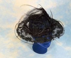 Edwardian era wire frame transparent wide brim vintage hat decorated with feathers and covered with crocheted lace appliques over black tulle.