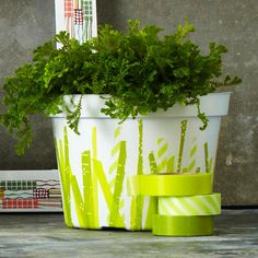 Give boring plastic pots instant personality with tape torn and attached to their surfaces. Here, tape in a variety of green hues and patterns mimics sprouting greenery