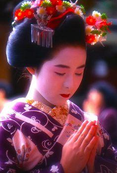 Maiko praying at Kitano Tenmangu shrine, Kyoto, Japan