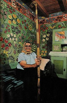 """April 1971 – """"A whole house for a canvas: Mrs. Lajosne Vargacz sits before a bedroom mural painted with the help of her neighbors at Kalocsa. Such folk art, once common in the region, today has few practitioners. Cane-and-feather duster resembles the long-handled paint brushes the artists used to decorate hard-to-reach heights."""" Via Sara Gossett"""