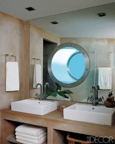 A stainless-steel porthole in the bath of a guest room of designers Antonio and Ignacio Saorin's vacation home on the island of Ibiza looks into the deep end of the swimming pool.