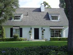 black shutters, painted brick, striped awnings, topiaries & clean evergreens