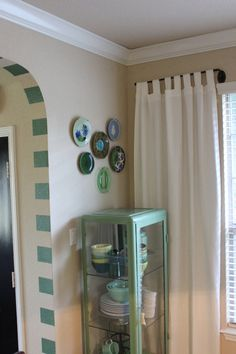 Plates from Anthropologie make great wall hangings in clusters. Latte Bowls in the curio in every shade of green. #AnthroFaves