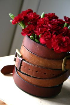 Love the tough-looking leather belt and fragile red carnations...wrap around an old vase and fill with flowers for a unique gift