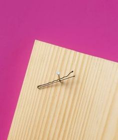 When working with a too-tiny-to-grip nail, slide it into the grooves of a bobby pin, then hold the end of the bobby pin as you hammer.