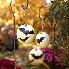 Transform white pumpkins into harvest moons using cardstock stencils. Just spray the pumpkins with a sealer, trace the pattern, and then fill in the outlines with black paint.