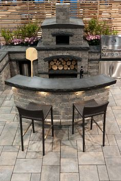 outdoor kitchen with a fireplace & a curved bar